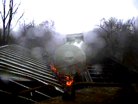 This is a still from video footage you are about to see, the tank car you are seeing is STILL moving being pushed by other freight cars on the track, the tank car seconds from hitting the back of the engine.